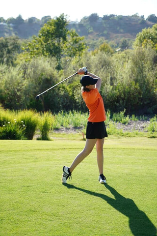 A woman wearing a black golf skort swinging her golf club on the course