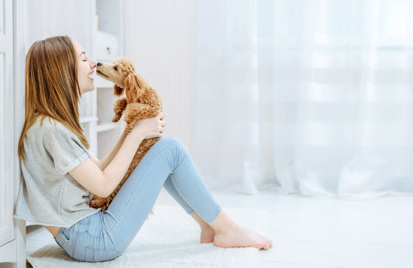 Smiling woman playing with her dog while sitting on the floor