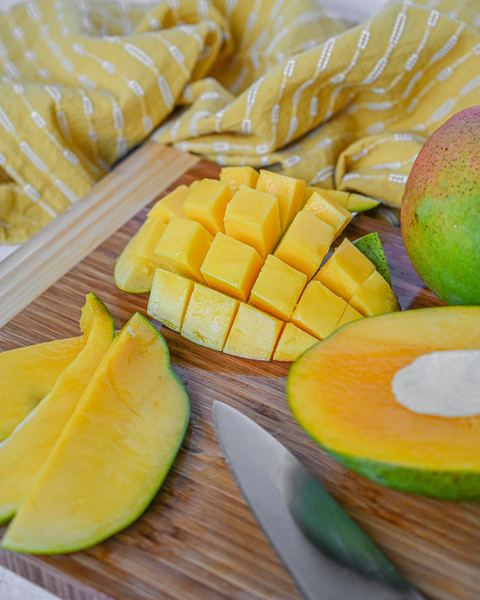 can dogs eat mango: Whole, sliced and diced mangoes and knife on a wooden board