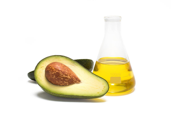 can dogs eat avocados: Flask of oil and an avocado sliced in half against a white background
