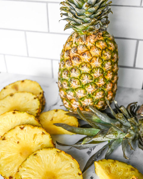 can dogs eat pineapple: Whole pineapple surrounded by pineapple slices on top of a marbled surface