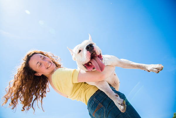 person happily carrying her dog