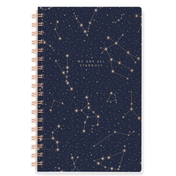 Fringe Studio We Are All Stardust Spiral bound, faux leather navy blue journal with a metallic gold stamped cover.