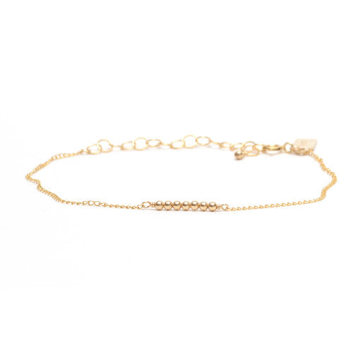 Favor Jewelry Ellipsis Bracelet.  Delicate gold bracelet with gold metal beads