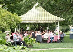 Out door gathering using a checkered white and green gazebo tent