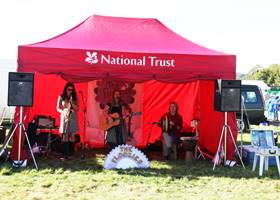 Live band using a red gazebo tent
