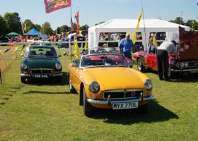 Yello vintage car and a big white gazebo tent