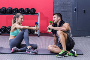 Couple sitting on mat in gym