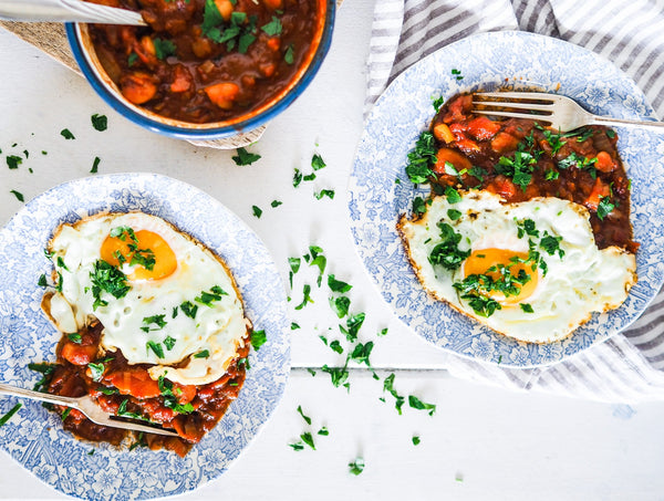 homemade baked beans on plates, topped with a fried egg and parsley. Gluten-free, refined sugar free and gut loving.