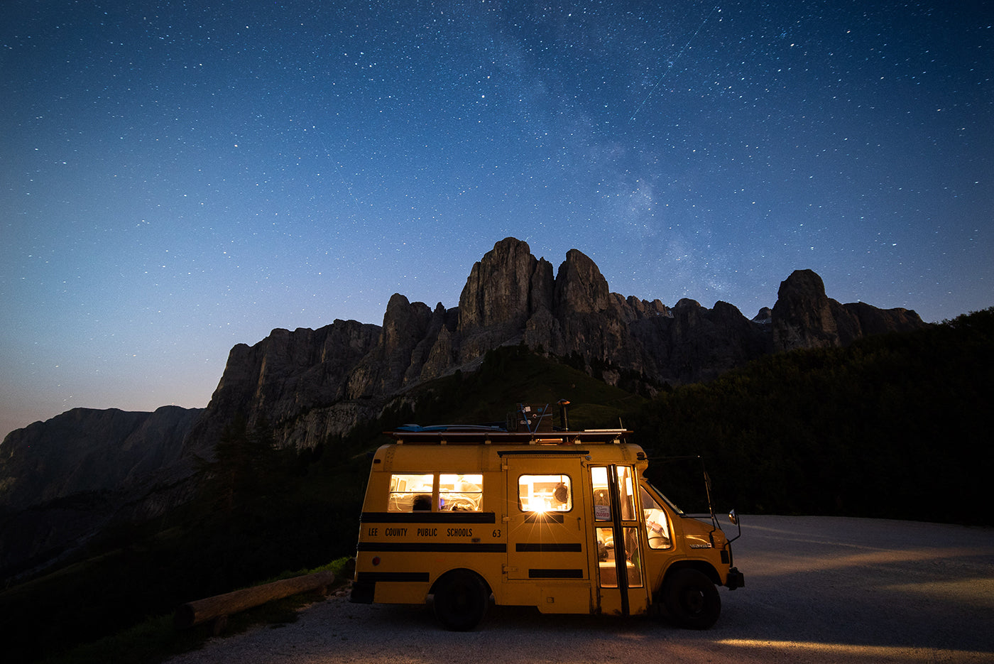 Lit school bus during night time. In the background a chain of mountains. (Photo: Kai Branss)