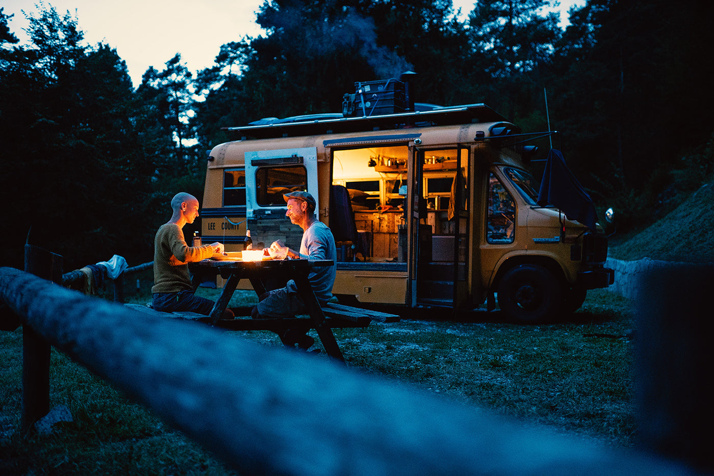 Kai Branss and his partner Julis sitting in front of their remodelled bus during night time. (Photo: Kai Branss)