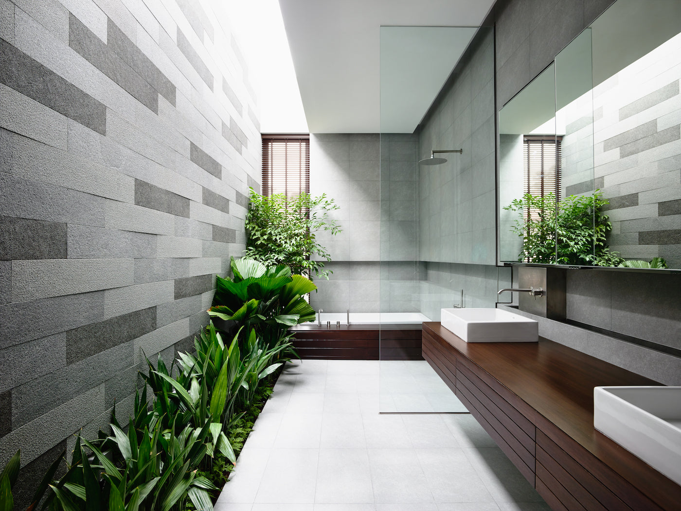 Green plants not only improve the air in interiors, but actually serve as decorative elements, too. This modern spacious bathroom is visually complemented by a mix of different types of leaves – big round, small ones, and those shaped like lancets.