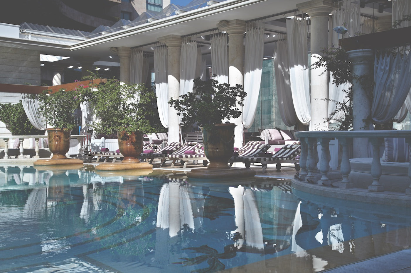 Spacious pool at Hote Phoenicia in Beirut. In the background, lounging furniture and curtains in front of large windows. (Photo: Monocle)