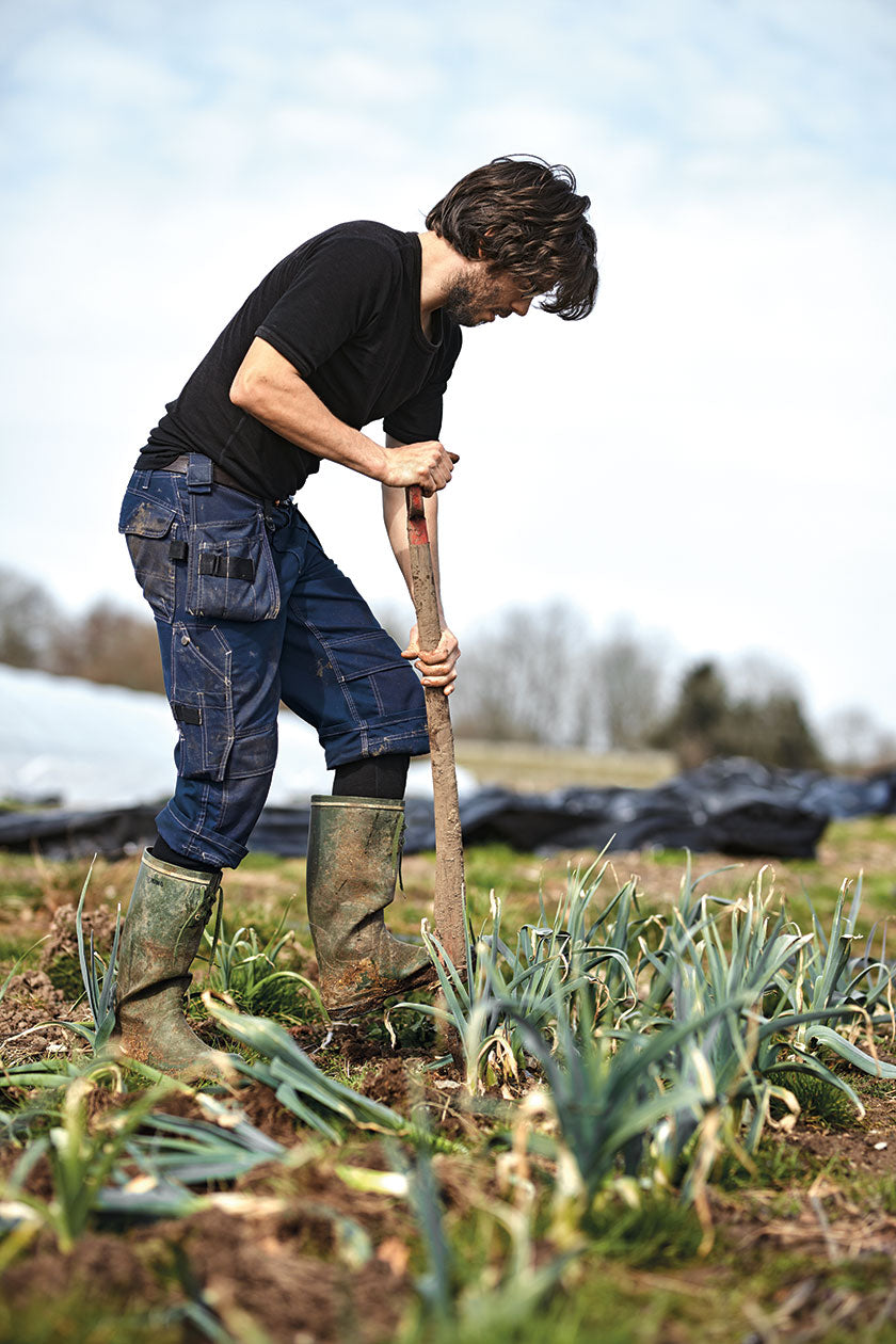 Chef and culinary entrepreneur Christian Puglisi has set up the Farm of Ideas, where vegetables are grown. Man with a shovel an a field of Farm of Ideas. (Photo: Michael Jepsen)