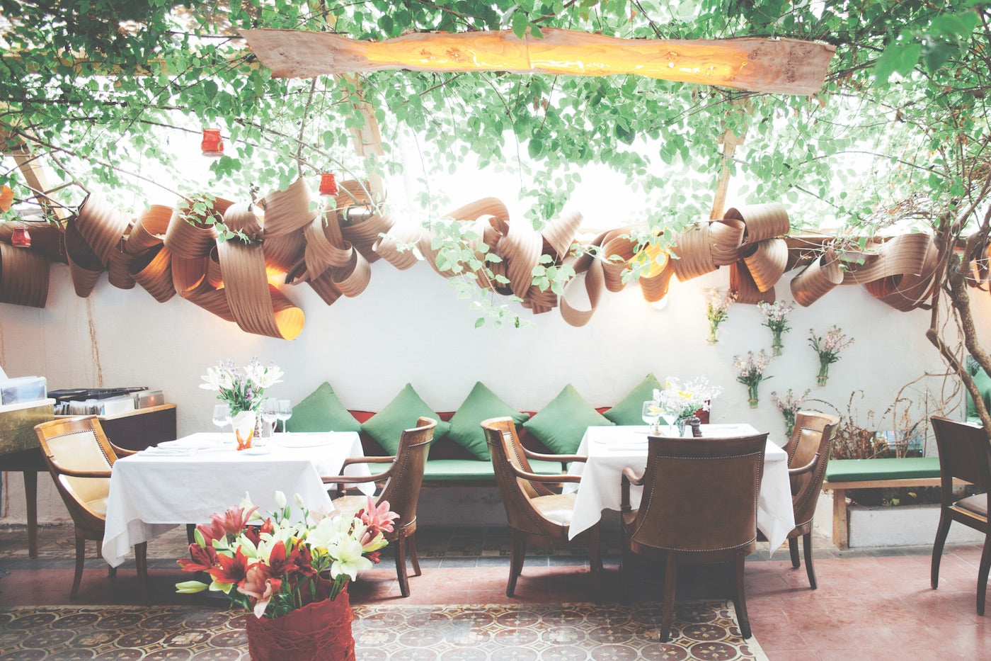 A set table with white linens at Villa Clara in Beirut. Flowers in the front and plants from the garden in the background of the picture. (Photo: Monocle)