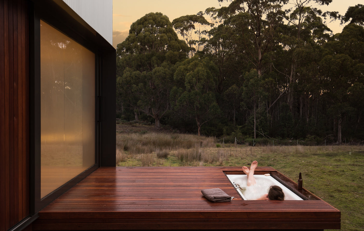 A bathtub is inserted into the floor of the outside deck of this cabin on Bruny Island (Tasmania, Australia). (Photo: Rob Maver)