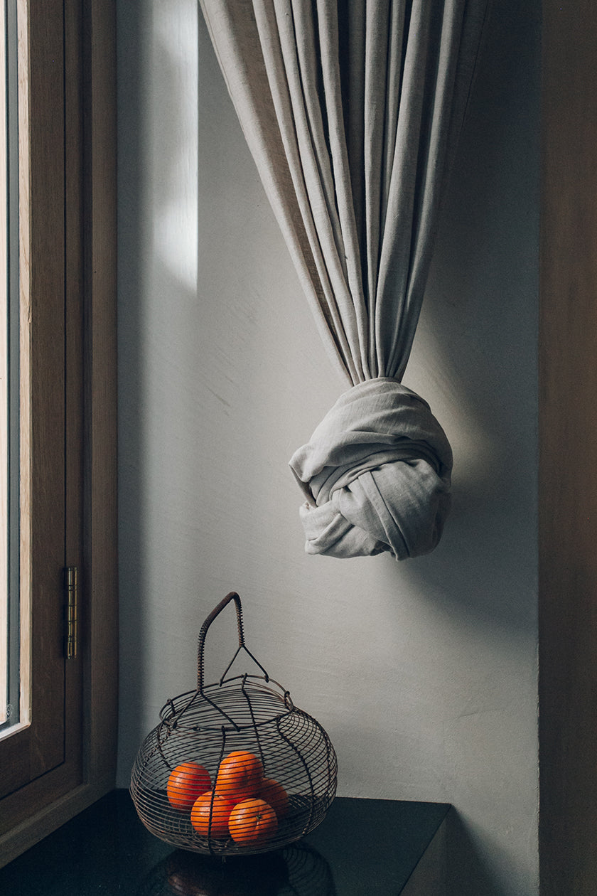 Basket with clementines and a knotted drape in front of a window in a studio designed by Izat and Arundell in Edinburgh. (Photo: Haarkon)