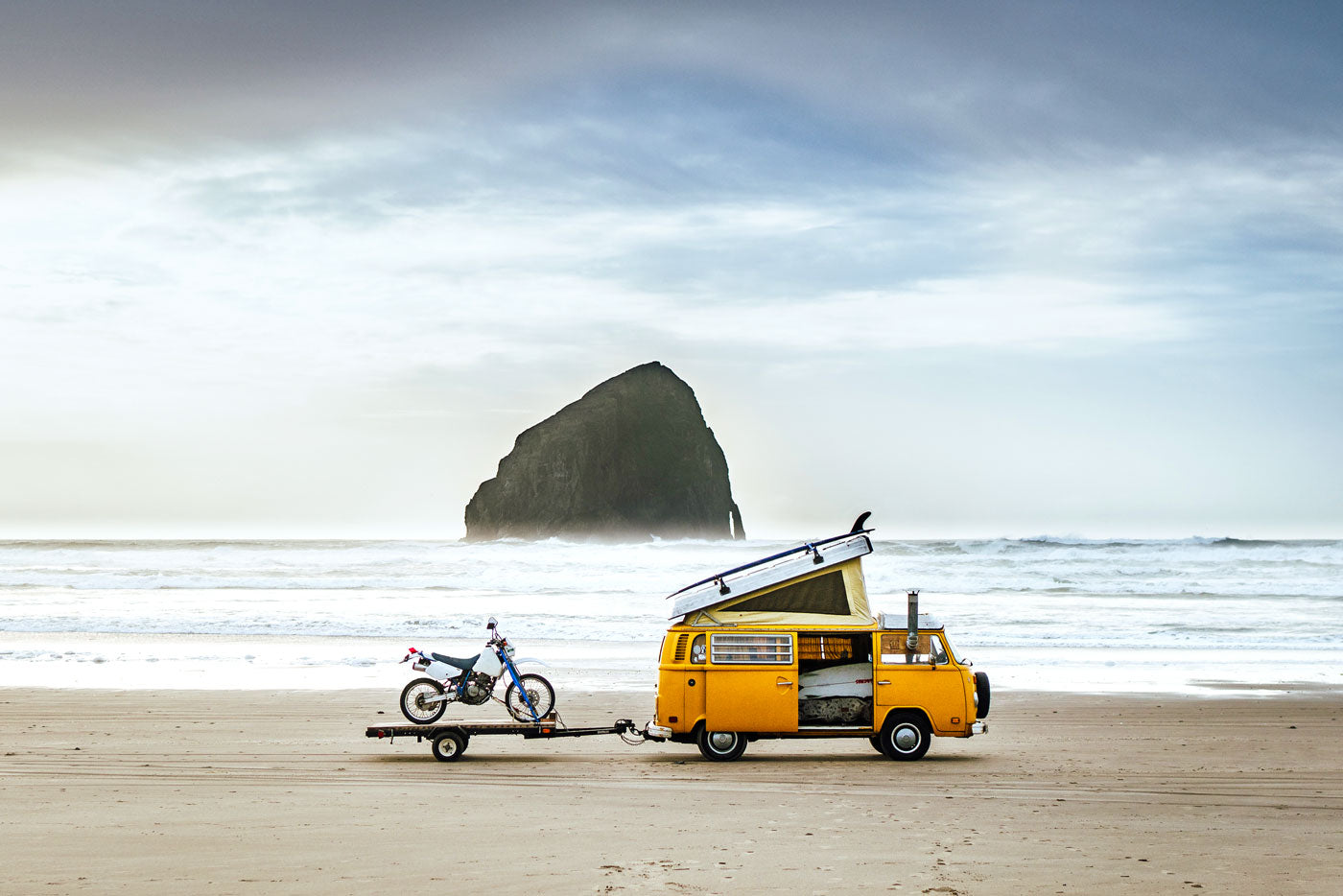 A van parked on a deserted beach. A motorcycle is parked on a hanger attached to the van. In the background is a rock formation in the ocean. (Photo: James Barkman)