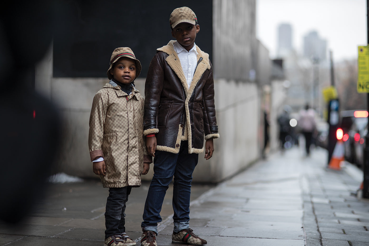 Two children standing on a sidewalk dressed in Gucci jackets in the streets of London. (Photo: Eva Losada)