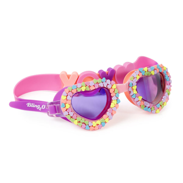 Purple and pink mixed coloured swimming googles with mini love heart details around lens and XOXO design on head strao