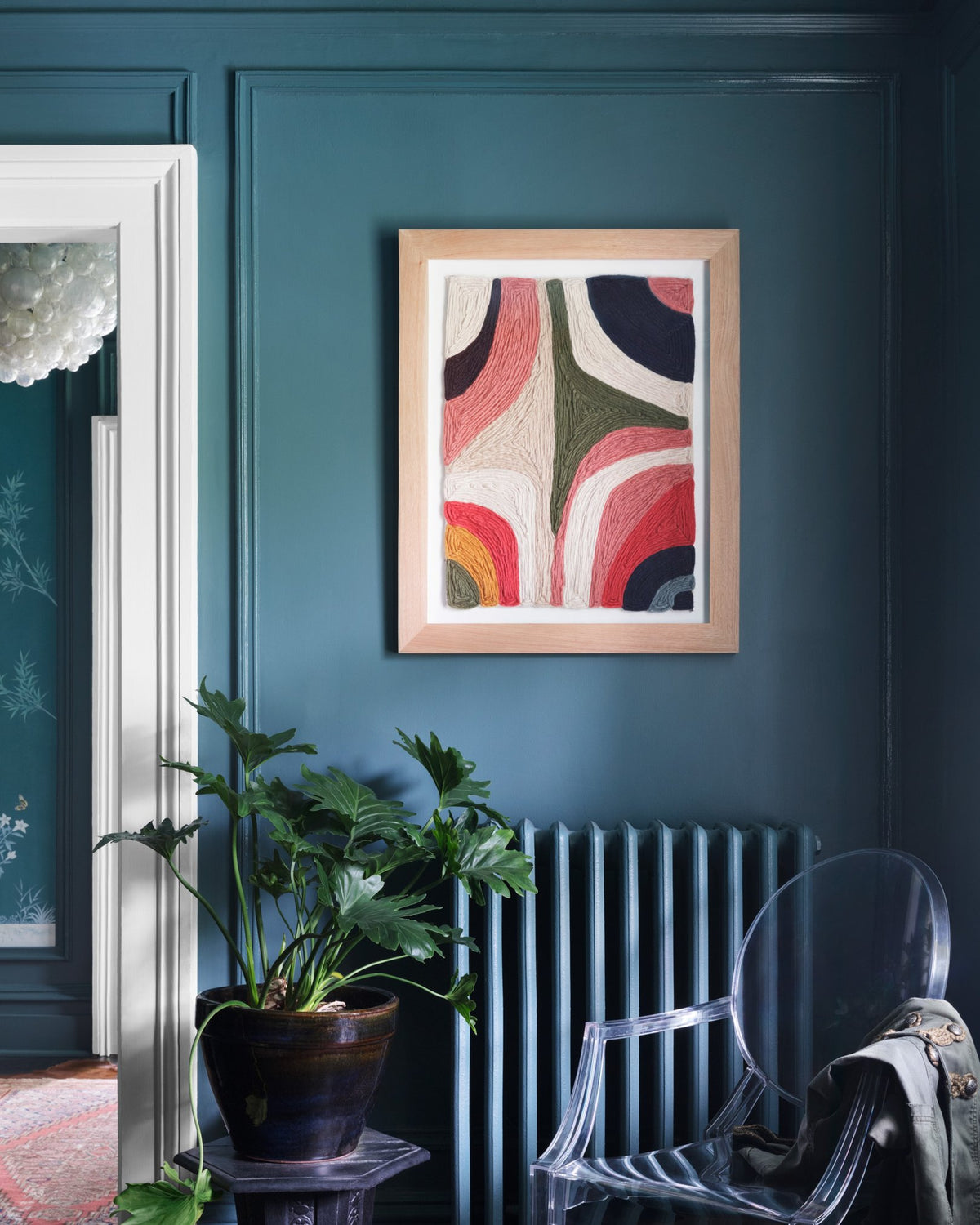 Framed wall art in navy room with plant