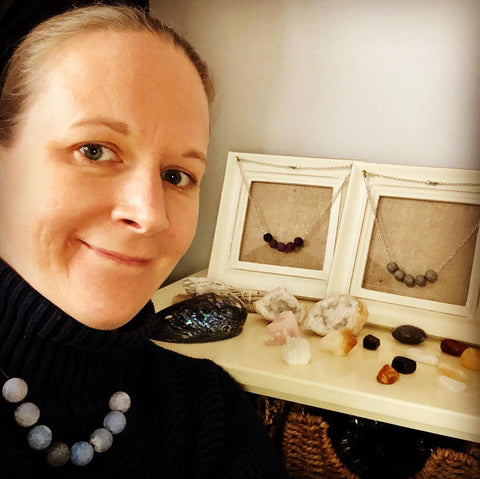 Image of Gemma in her studio with her handmade necklace designs and crystal collection in background