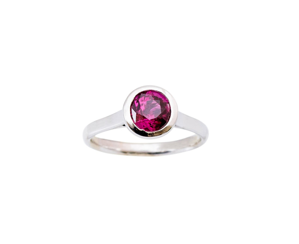 This ring was designed and made in our store. 14k white gold bezel setting mounting.  One round faceted rhodolite garnet.