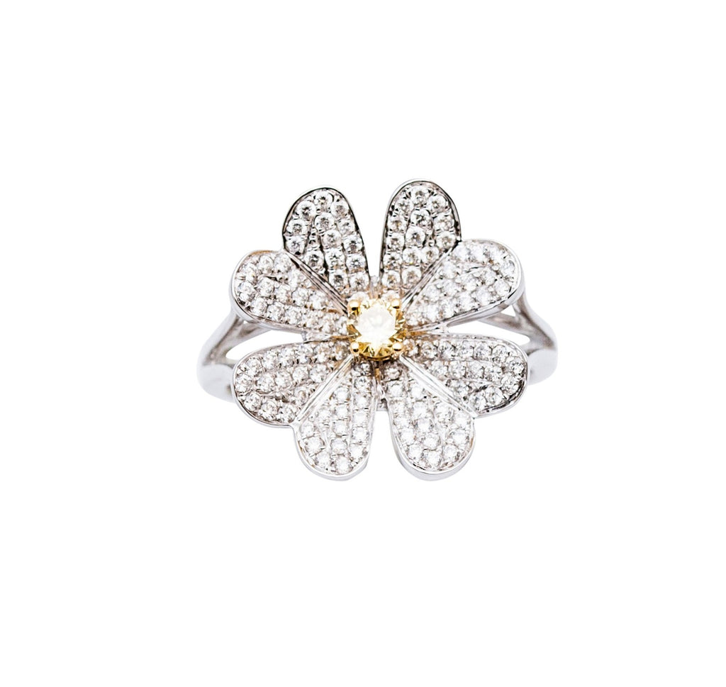 This whimsical daisy ring has120 round white diamonds  0.66 cts An eye catching yellow diamond center 0.15 cts  Set in 18k white gold mounting  6.5 sizeable ring  17.63 mm