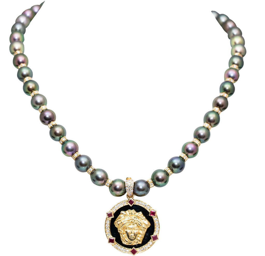 "18k yellow gold Versace style charm with gallery finish at the back, set in onyx background, surrounded diamonds 0.10 cts and 6 rubys 0.80 cts. 27.00 mm size 8.00 mm enhancer bail 18k yellow gold with diamonds  Pearl necklace sold separately; 8.81 mm black pearls with 20 yellow gold diamond rondels 2.0 cts and secure 18k yellow gold diamond catch  Pearl necklace 325-81 $4799.00 16"" long"