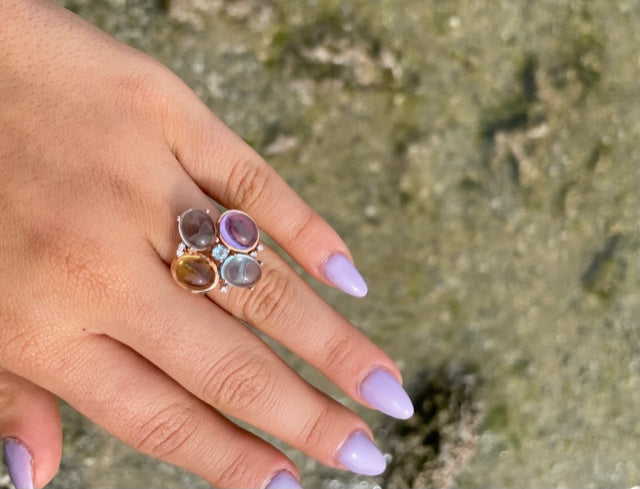 Set in 14k rose gold  4 cabochon stones; amethyst, blue topaz, citrine & moonstone   Five small round diamonds  Size 6 (sizeable)