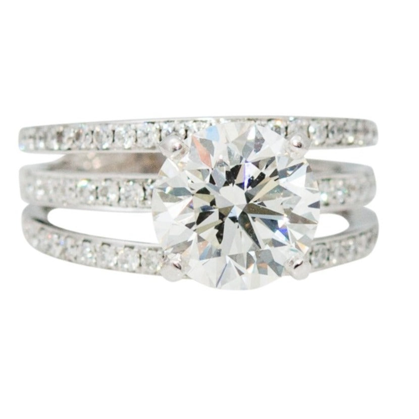 Brilliant cut stone 2.73 cts set in three diamond band 1.0 cts in small round diamonds set in a platinum mounting.