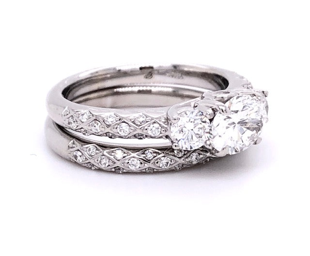 This East-West setting is an unconventional setting that is gaining popularity. This type of setting highlights the wedding band. Comfort is also a great benefit from this style..  GIA certified Oval cut diamond 0.98 cts  Color F  Clarity SI2  Set in 18k white gold contemporary mounting with two round diamonds for side stones 0.40 cts. Matching band 18k white gold adorned with filigree style 0.90 cts total