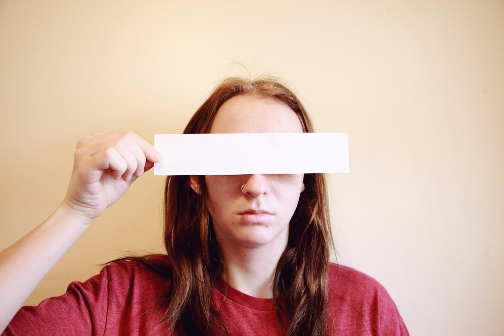 woman holding paper in front of her eyes