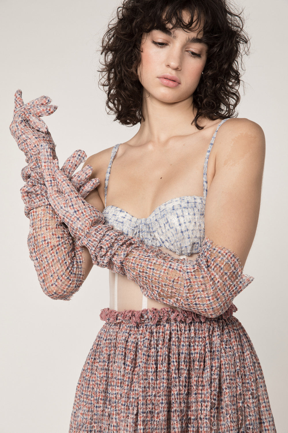 Rosie Assoulin Pre-Fall 2019 The Undress. Mid-length cocktail dress with sheer panels. Corset bodice. Scalloped hem. Ruffle detail at waist. Red plaid. 60% Nylon, 40% Rayon. Sizes 0 - 12.
