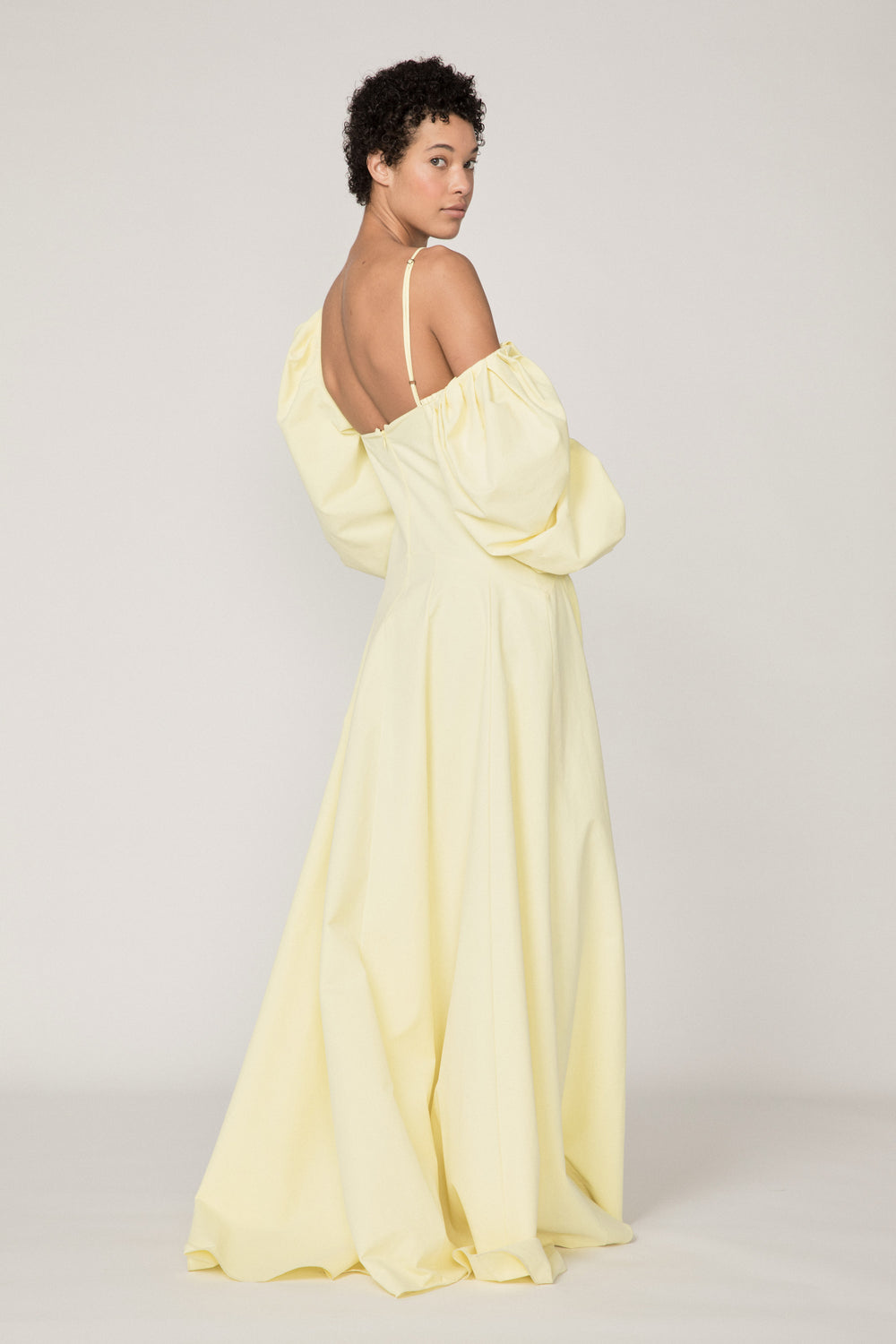 Rosie Assoulin Pre-Fall 2019 Ups and Downs Gown. Asymmetrical off-the-shoulder cami gown. Adjustable shoulder straps. Elasticized balloon sleeves. Invisible zipper in back. Yellow. 100% Cotton. Sizes 0 - 12.