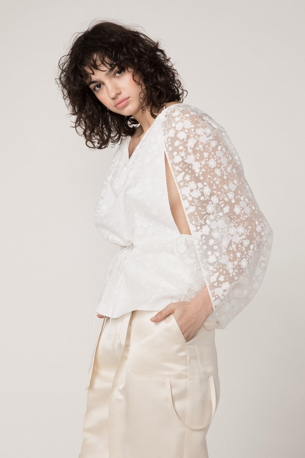 Rosie Assoulin Pre-Fall 2019 Cape Top. Drapey top with sheer sleeves. Drawstring waist. Scooped open back. White. 76% Cotton, 22% Polyester, 2% Elastane. Sizes XS - L.