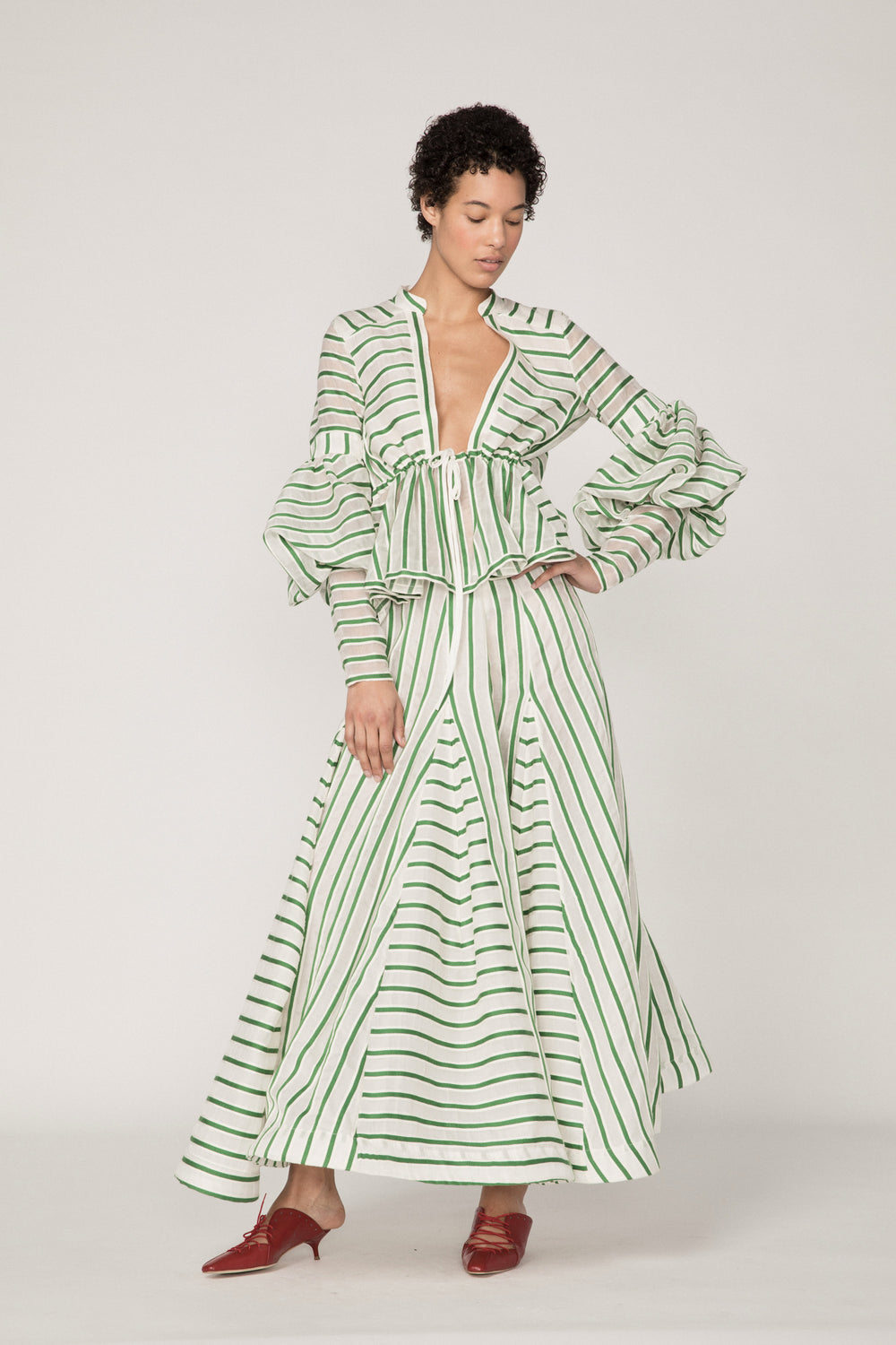 Rosie Assoulin Pre-Fall 2019 Lantern Sleeve Top. V-neck peplum top. Low neckline. Hook and eye closures. Voluminous sleeves. Green stripe. 77% Virgin Wool, 23% Silk. Sizes XS - L.
