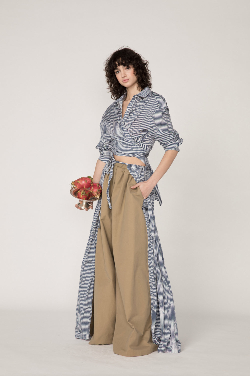 Rosie Assoulin Pre-Fall 2019 Superhero Pant II. Wide leg pants with caped skirting. Ties in front. Adjustable drawstring waist. Khaki. 100% Cotton. Sizes 0 - 12.