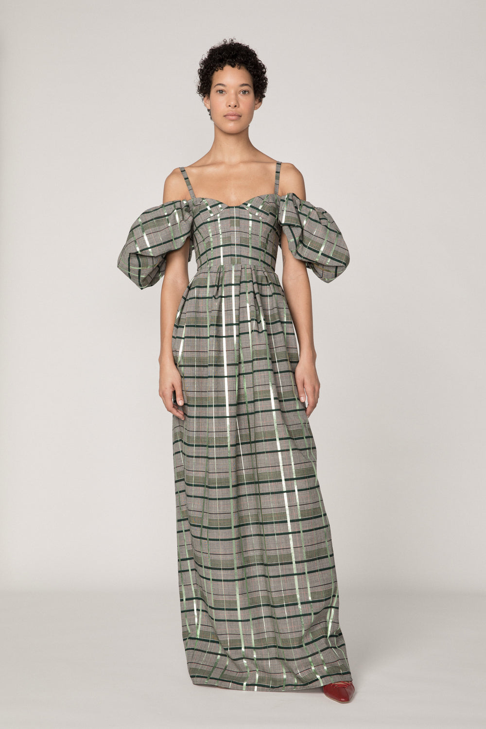 Rosie Assoulin Fall 2019 Off The Shoulder Puff Sleeve Gown. Full-length wool gown with puff sleeves. Ruched skirt. Split seam on rear hem. Center back zipper. Finished with metallic foil. Green plaid. 98% Wool, 2% Polyester. Sizes 0 - 12.