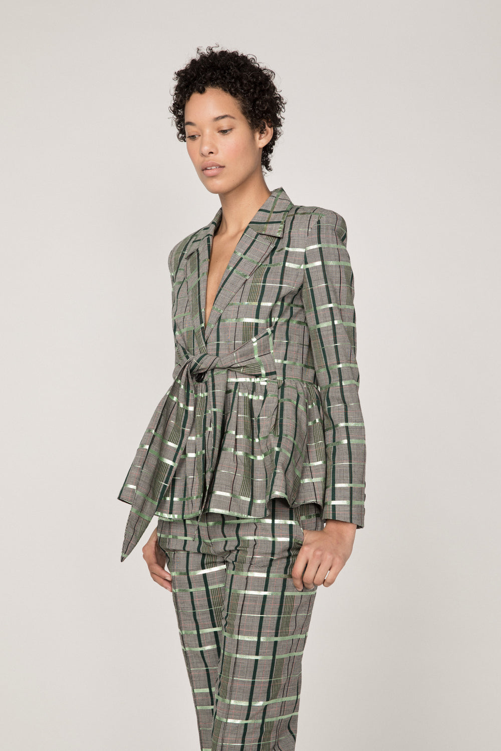Rosie Assoulin Fall 2019 Tie-Front Peplum Blazer. Flared blazer. Tie-front detail. Buttons along cuff. Finished with metallic foil. Green plaid. 98% Wool, 2% Polyester. Sizes 0 - 12.
