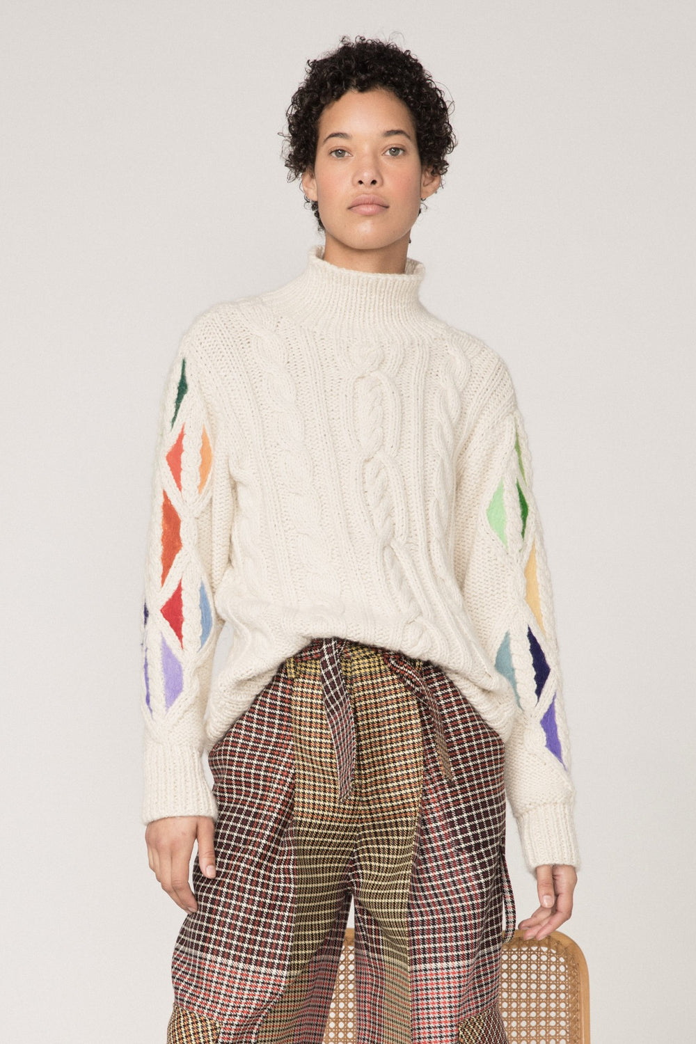 Rosie Assoulin Fall 2019 Knit Pain in the Glass Sweater. Traditional cableknit sweater. Needle-felted rainbow panels on sleeves. Mock neckline. Oversized fit. Cream. 100% Baby Alpaca Wool. Sizes XS - L.