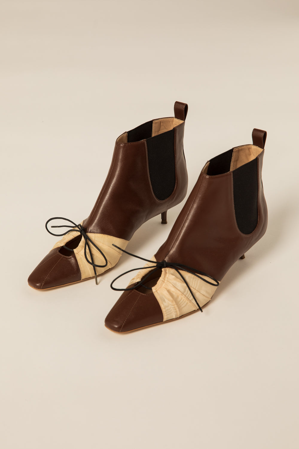 "Rosie Assoulin Fall 2019 Pleated Ankle Booties. Kitten heeled ankle boot. Adjustable front laces. Keyhole cutout. Elastic stretch panels. Pull tab in back. 1.5"" heel. Brown. Sizes 35 - 41."