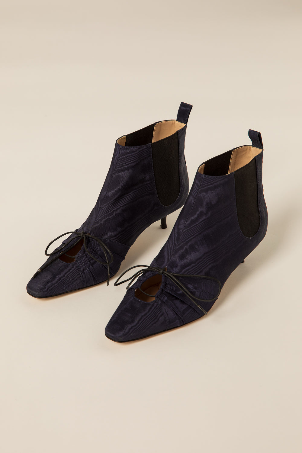 "Rosie Assoulin Fall 2019 Pleated Ankle Booties. Kitten heeled ankle boot. Adjustable front laces. Keyhole cutout. Elastic stretch panels. Pull tab in back. 1.5"" heel. Navy. Sizes 35 - 41."