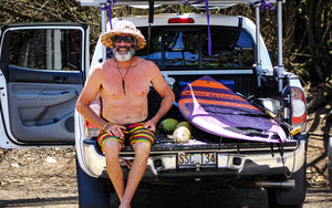 Carlos sitting in a truck next to the Carve surf SUP