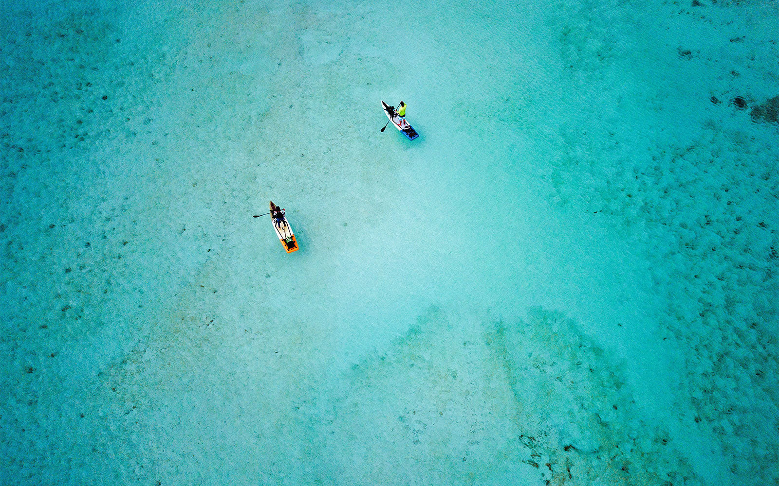 inflatable paddle boards being paddled over some blue waters
