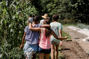 Campers walking through the garden with arms on each others' shoulders