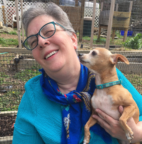 Head shot photo of author J. M. Silverleaf holding her pet Chihuahua.  She is wearing blue rimmed glasses, and an aqua short with a deep blue patterned scarf.