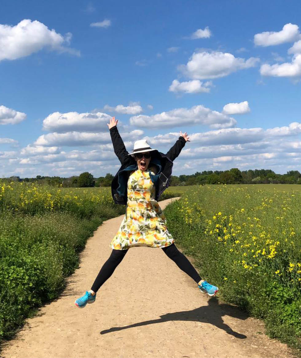 Tara Button leaping for joy in an English country field.