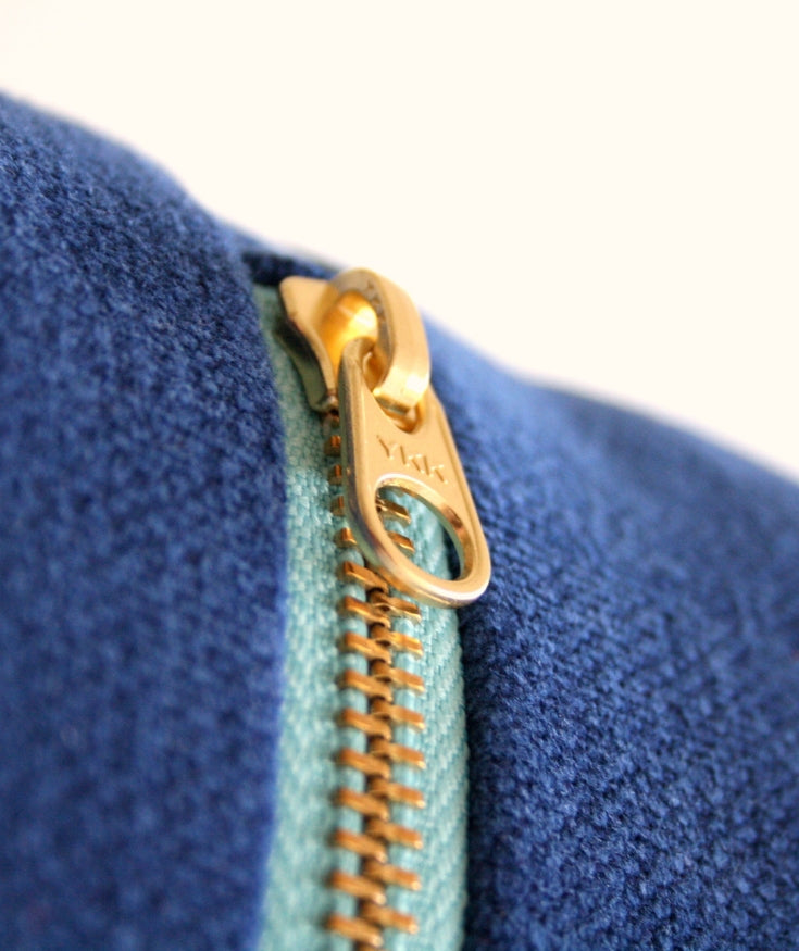 A YKK zipper attached to a pair of denim jeans