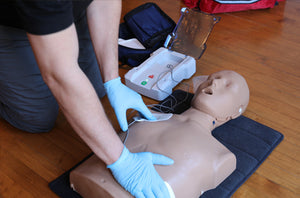 AED being placed on first aid dummy
